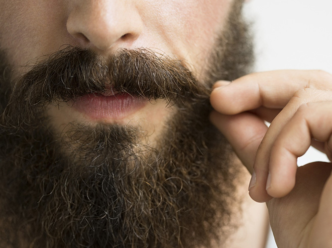 Close up of man touching mustache